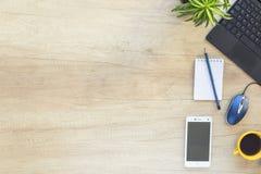 Πίνακας γραφείων γραφείων με το lap-top, τις προμήθειες και το smartphone Τοπ άποψη με το διάστημα αντιγράφων στοκ εικόνες