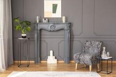 Πίνακας δίπλα στην γκρίζα πολυθρόνα στο κομψό εσωτερικό καθιστικών με Στοκ Εικόνες