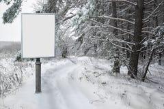 Πίνακας διαφημίσεων για τη διαφήμιση στο υπόβαθρο του χιονώδους δασικού τοπίου Στοκ Εικόνα