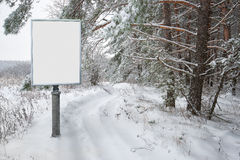 Πίνακας διαφημίσεων για τη διαφήμιση στο υπόβαθρο του χιονώδους δασικού τοπίου Στοκ φωτογραφία με δικαίωμα ελεύθερης χρήσης