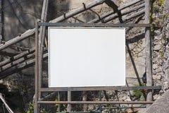 Πίνακας διαφημίσεων κοντά σε ένα εγκαταλειμμένο σπίτι στοκ εικόνες με δικαίωμα ελεύθερης χρήσης