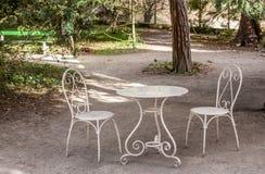 Πίνακας και άσπρες καρέκλες στον κήπο Στοκ φωτογραφία με δικαίωμα ελεύθερης χρήσης