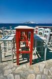 Πίνακας και ελληνικό taverna καρεκλών στην προκυμαία Στοκ Εικόνες