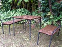 Πίνακας και καρέκλα πλαισίων μετάλλων που τίθενται στον κήπο στοκ εικόνα με δικαίωμα ελεύθερης χρήσης