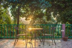 Πίνακας και καρέκλα στην ξύλινη γέφυρα στον κήπο με το ηλιοβασίλεμα στοκ φωτογραφία