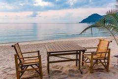 Πίνακας και καρέκλες στην ανατολή σε μια παραλία tanquil στην Ταϊλάνδη Στοκ Εικόνες