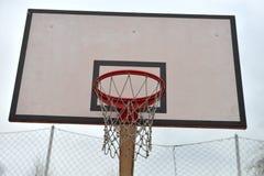 Πίνακας καλαθοσφαίρισης κάτω από το νεφελώδη ουρανό σε ένα σχολικό ναυπηγείο Έννοια του Κ Στοκ εικόνες με δικαίωμα ελεύθερης χρήσης