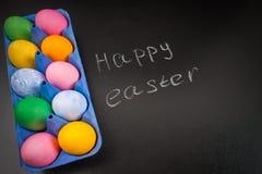 Πίνακας κιμωλίας ευτυχές Πάσχα κιμωλίας σε έναν πίνακα κιμωλίας και ζωηρόχρωμα αυγά Στοκ Εικόνες