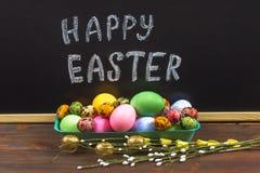 Πίνακας κιμωλίας ευτυχές Πάσχα κιμωλίας σε έναν πίνακα κιμωλίας και ζωηρόχρωμα αυγά Στοκ εικόνα με δικαίωμα ελεύθερης χρήσης