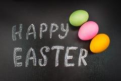 Πίνακας κιμωλίας ευτυχές Πάσχα κιμωλίας σε έναν πίνακα κιμωλίας και ζωηρόχρωμα αυγά Στοκ φωτογραφίες με δικαίωμα ελεύθερης χρήσης
