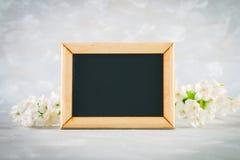 Πίνακας κιμωλίας σε ένα ξύλινο πλαίσιο με ένα κενό κιβώτιο που περιβάλλεται από τα άσπρα λουλούδια σε ένα γκρίζο υπόβαθρο Αντιγρά Στοκ εικόνα με δικαίωμα ελεύθερης χρήσης