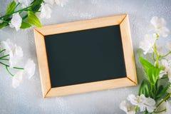Πίνακας κιμωλίας σε ένα ξύλινο πλαίσιο με ένα κενό κιβώτιο που περιβάλλεται από τα άσπρα λουλούδια σε ένα γκρίζο υπόβαθρο Αντιγρά Στοκ Φωτογραφία