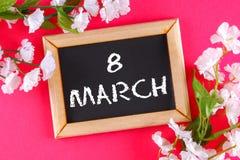 Πίνακας κιμωλίας σε ένα ξύλινο πλαίσιο που περιβάλλεται από τα άσπρα λουλούδια σε ένα ρόδινο υπόβαθρο 8 Μαρτίου, ημέρα γυναικών Στοκ Εικόνα
