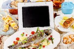 Πίνακας κιμωλίας στον πίνακα με το ψημένο στη σχάρα γεύμα θαλασσινών Στοκ φωτογραφία με δικαίωμα ελεύθερης χρήσης