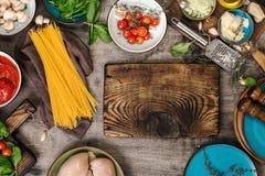 Πίνακας κουζινών με τα ακατέργαστα μακαρόνια και συστατικά για το χορευτικό βήμα μαγειρέματος στοκ εικόνα