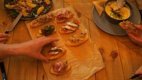 Πίνακας με τα τρόφιμα και τα ποτήρια του χυμού, χέρια της κατανάλωσης των ανθρώπων απόθεμα βίντεο