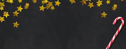 Πίνακας με τα χρυσά αστέρια και έναν κάλαμο καραμελών Στοκ Εικόνες
