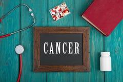 Πίνακας με το κείμενο & x22 Cancer& x22 , βιβλίο, χάπια και στηθοσκόπιο στο μπλε ξύλινο υπόβαθρο στοκ εικόνα