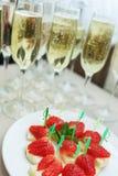 Πίνακας μπουφέδων με τις φρέσκες φράουλες στο πρόχειρο φαγητό και τη σαμπάνια ανανά Στοκ Εικόνα