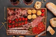Πίνακας ορεκτικών με το antipasti, το τυρί, charcuterie, τα πρόχειρα φαγητά και το κρασί differents Μίνι burgers, λουκάνικο, ζαμπ Στοκ Φωτογραφία