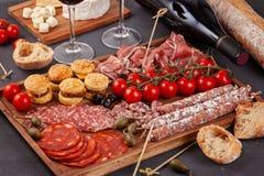 Πίνακας ορεκτικών με το antipasti, το τυρί, charcuterie, τα πρόχειρα φαγητά και το κρασί differents Μίνι burgers, λουκάνικο, ζαμπ Στοκ εικόνες με δικαίωμα ελεύθερης χρήσης
