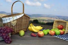 Πίνακας πικ-νίκ με δύο καλάθια και φρούτα και το τοπίο βουνών Στοκ Φωτογραφίες