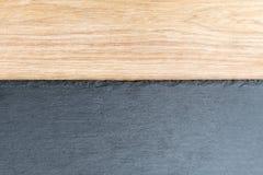 Πίνακας πλακών στο ξύλινο υπόβαθρο Μαύρη και γκρίζα κατασκευασμένη επίπεδη πέτρα πλακών που βάζει στο καφετί ξύλινο επιτραπέζιο υ Στοκ Φωτογραφία