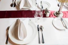 Πίνακας που θέτει για ένα καλό γεύμα κενό σύνολο εστιατορίων γυαλιών εσωτερικό μέρος πετσέτες, πιάτα, και μαχαιροπήρουνα Στοκ Εικόνα