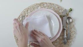 Πίνακας που θέτει με τα άσπρα πιάτα στο άσπρο υπόβαθρο Η γυναίκα διπλώνει υπέροχα την πετσέτα στο πιάτο Κομψός πίνακας απόθεμα βίντεο