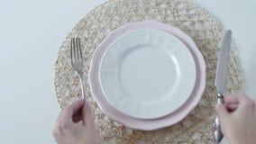 Πίνακας που θέτει με τα άσπρα πιάτα στο άσπρο υπόβαθρο Η γυναίκα διπλώνει υπέροχα την πετσέτα στο πιάτο Κομψός πίνακας φιλμ μικρού μήκους
