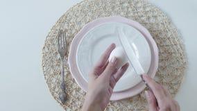Πίνακας που θέτει με τα άσπρα πιάτα στο άσπρο υπόβαθρο Το βρασμένο αυγό για τα θηλυκά χέρια προγευμάτων γεννά ένα αυγό σε ένα πιά φιλμ μικρού μήκους