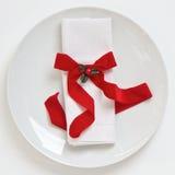 Πίνακας που θέτει με την κόκκινη κορδέλλα Χριστουγέννων Στοκ φωτογραφία με δικαίωμα ελεύθερης χρήσης