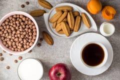 Πίνακας προγευμάτων με τον καφέ, τα μπισκότα πιπεροριζών, τις σφαίρες δημητριακών σοκολάτας, το γάλα και τα φρούτα στο υπόβαθρο π Στοκ Εικόνες