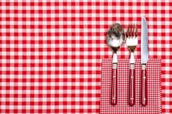 Πίνακας σε ένα εστιατόριο με τα μαχαιροπήρουνα στο κόκκινο Στοκ Εικόνα