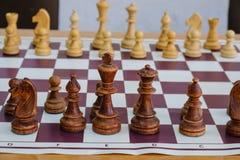 Πίνακας σκακιού με τα κομμάτια και ρολόι στο ξύλινο γραφείο σχετικά με τα πρωταθλήματα σκακιού Στοκ Φωτογραφίες