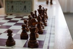 Πίνακας σκακιού με τα κομμάτια και ρολόι στο ξύλινο γραφείο σχετικά με τα πρωταθλήματα σκακιού Στοκ φωτογραφία με δικαίωμα ελεύθερης χρήσης