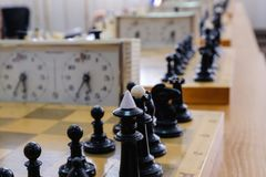 Πίνακας σκακιού με τα κομμάτια και ρολόι στο ξύλινο γραφείο σχετικά με τα πρωταθλήματα σκακιού Στοκ φωτογραφίες με δικαίωμα ελεύθερης χρήσης
