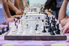 Πίνακας σκακιού με τα κομμάτια και ρολόι στο ξύλινο γραφείο σχετικά με τα πρωταθλήματα σκακιού Στοκ Εικόνες