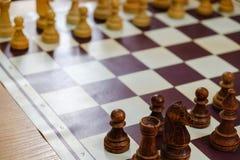 Πίνακας σκακιού με τα κομμάτια και ρολόι στο ξύλινο γραφείο σχετικά με τα πρωταθλήματα σκακιού Στοκ Εικόνα