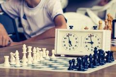 Πίνακας σκακιού με τα κομμάτια σκακιού και ρολόι σκακιού στο ξύλινο γραφείο μέσα Στοκ Φωτογραφίες