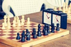 Πίνακας σκακιού με τα κομμάτια σκακιού και ρολόι σκακιού στο ξύλινο γραφείο μέσα Στοκ φωτογραφίες με δικαίωμα ελεύθερης χρήσης