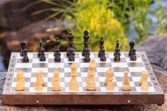 Πίνακας σκακιού με τα κομμάτια σκακιού στο βράχο με την πλάτη αναχωμάτων ποταμών Στοκ φωτογραφία με δικαίωμα ελεύθερης χρήσης