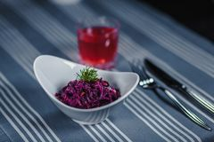 Πίνακας στο εστιατόριο Στον πίνακα είναι μια σαλάτα σε ένα άσπρο πιάτο, ένα μαχαίρι, ένα δίκρανο, ένα γυαλί με τον κόκκινο χυμό Σ Στοκ φωτογραφία με δικαίωμα ελεύθερης χρήσης