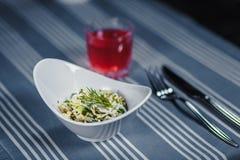 Πίνακας στο εστιατόριο Στον πίνακα είναι μια σαλάτα σε ένα άσπρο πιάτο, ένα μαχαίρι, ένα δίκρανο, ένα γυαλί με τον κόκκινο χυμό Σ Στοκ Φωτογραφίες