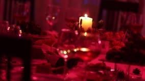 Πίνακας συμποσίου σε ένα εστιατόριο με τα γυαλιά και ένα κερί, ένα γυαλί με το κόκκινο και άσπρο κρασί σε έναν πίνακα συμποσίου σ φιλμ μικρού μήκους