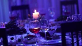 Πίνακας συμποσίου σε ένα εστιατόριο με τα γυαλιά και ένα κερί, ένα γυαλί με το κόκκινο και άσπρο κρασί σε έναν πίνακα συμποσίου σ απόθεμα βίντεο