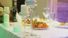 Πίνακας συμποσίου σε ένα εστιατόριο με τα γυαλιά και ένα κερί, ένα διακοσμητικό κερί κεριών στο κρεμαστό κόσμημα σε έναν πίνακα φιλμ μικρού μήκους