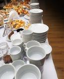Πίνακας συμποσίου τομέα εστιάσεως με τα ψημένα πρόχειρα φαγητά, τα σάντουιτς, τα κέικ, τα φλυτζάνια και τα πιάτα τροφίμων Στοκ Φωτογραφίες