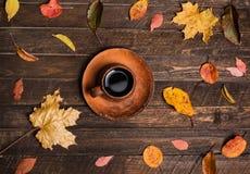 Πίνακας φθινοπώρου σε ένα υπαίθριο café Φύλλα φθινοπώρου και φλυτζάνι ο καφέ Στοκ Εικόνες