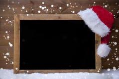Πίνακας Χριστουγέννων, καπέλο Santa, διάστημα αντιγράφων, χιόνι, Snowflakes Στοκ Εικόνες